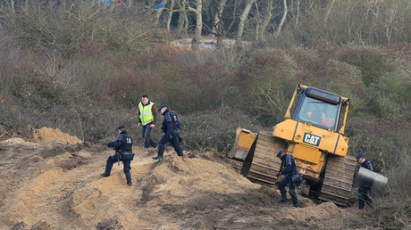 French police officers secure the area as a bulldozer is used to clear dismantled shelters of the camp known as the