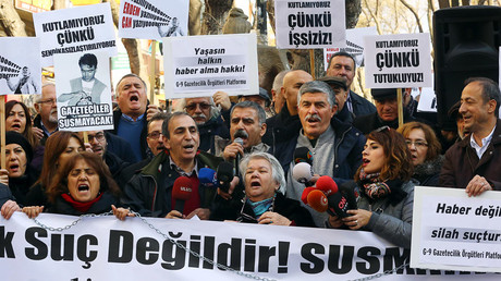 Turkish journalists hold banners and shout slogans during a demonstration in support of jailed journalists Can Dundar and Erdem Gul on January 10, 2016 in Ankara during the