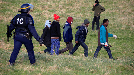 A French riot policeman stops migrants in a field near Calais, France, as migrants gather in the hopes of attempting to board lorries and making their way across the Channel to Britain © Pascal Rossignol