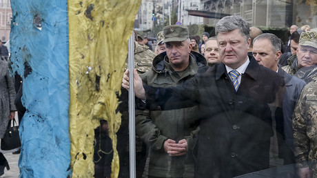 Ukraine's President Petro Poroshenko (C) looks at a Ukrainian flag brought from an eastern region of the country where a military conflict took place, during his visit to an exhibition of new Ukrainian military equipment in Kiev, Ukraine © Gleb Garanich