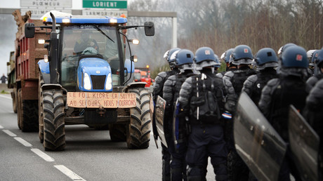 French gendarmes stand on the RN 165 motorway facing protesters in a tractor, Lorient, western France, January 25, 2016, during a protest against the falling prices of dairy and meat products. © Jean-Sebastien Evrard