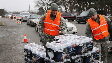 Michigan National Guard members help to distribute water to a line of residents in their cars in Flint, Michigan January 21, 2016. © Rebecca Cook