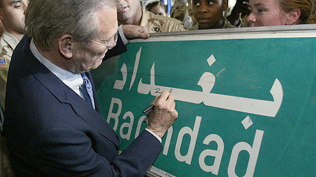 U.S. Secretary of Defence Donald Rumsfeld (C) signs a Baghdad road sign