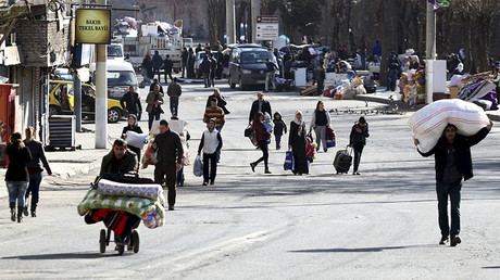 Residents carry their belongings as they flee from Sur district, which is partially under curfew, in the Kurdish-dominated southeastern city of Diyarbakir, Turkey January 27, 2016. ©Sertac Kayar
