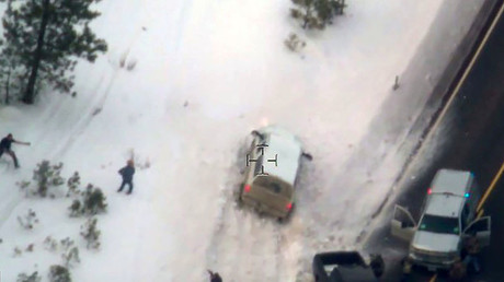 Aerial video released by the FBI January 28, 2016 shows a law enforcement officer (L) pointing a weapon at a man who had just stepped out of the white pickup truck at a police roadblock January 26 near Burns, Oregon. © FBI
