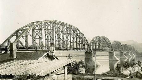 One striking image shows the girl posing on a rooftop in front of famous Krasnoyarsk Railway Bridge, opened in 1899, which carries the Trans Siberian railway over the Yenisei River © Krasnoyarsk Regional Museum / The Siberian Times