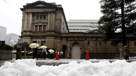 People holding umbrellas walk in front of the Bank of Japan building after snowfall in Tokyo, Japan  © Toru Hanai