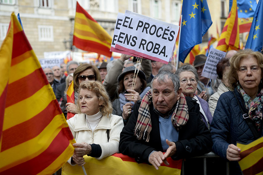 """A woman holds placards reading in Catalan """"The Process Steals Us"""" as other emonstrators wave European, Spanish and Catalan flags during a demonstration called by """"Sociedat Civil Catalana"""" to support the unity of Spain, at Catalonia square in Barcelona, on January 31, 2016. © Josep Lago"""