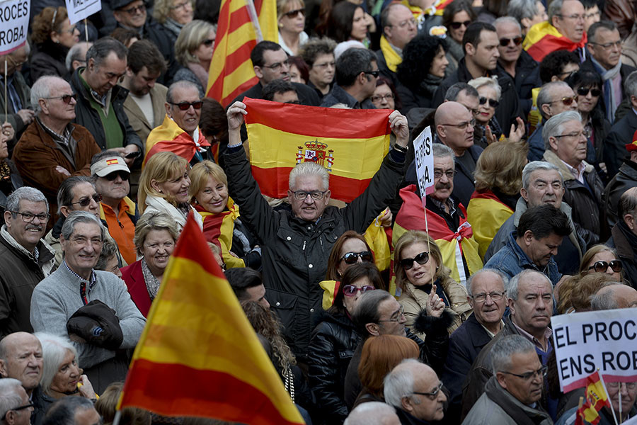 """A man holds a Spanish flag during a demonstration called by """"Societat Civil Catalana"""" (Catalan Civil Society) to support the unity of Spain, at Catalonia square in Barcelona, on January 31, 2016. ©© Josep Lago"""