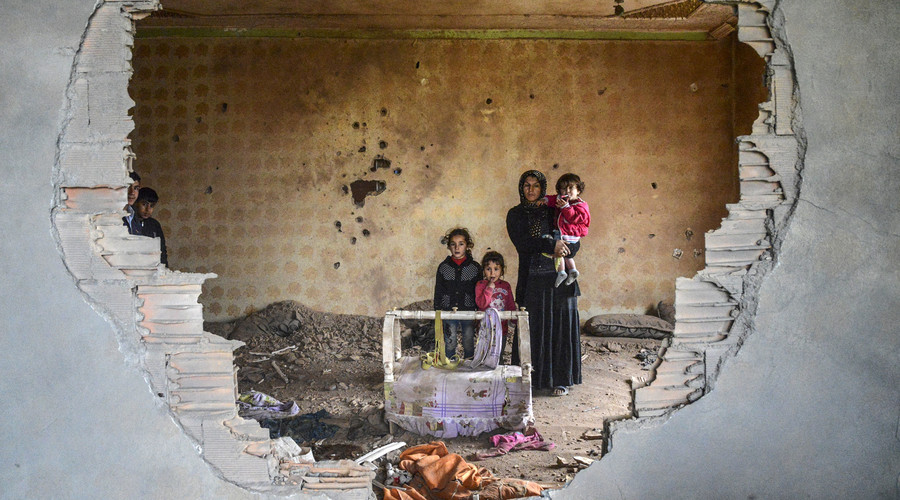 A women and her children stand in the ruins of battle-damaged house in the Kurdish town of Silopi, in southeastern Turkey, near the border with Iraq on January 19, 2016. © Ilyas Akengin