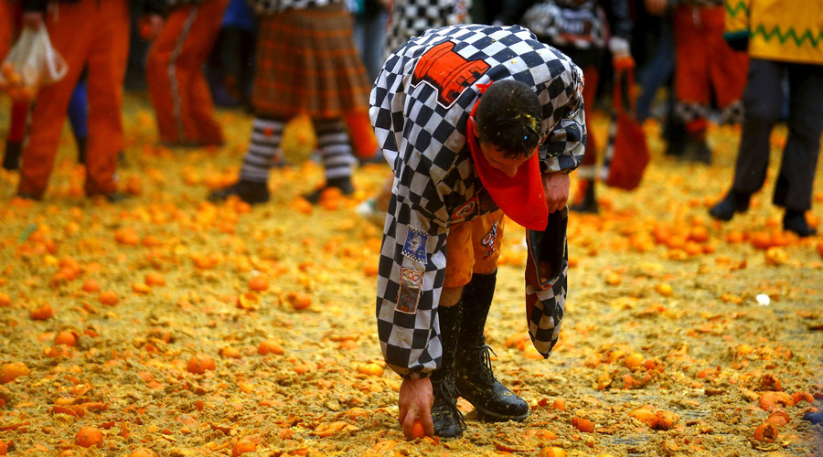 A member of a rival team collects a orange from the ground during an annual carnival battle in the northern Italian town of Ivrea February 7, 2016. © Stefano Rellandini