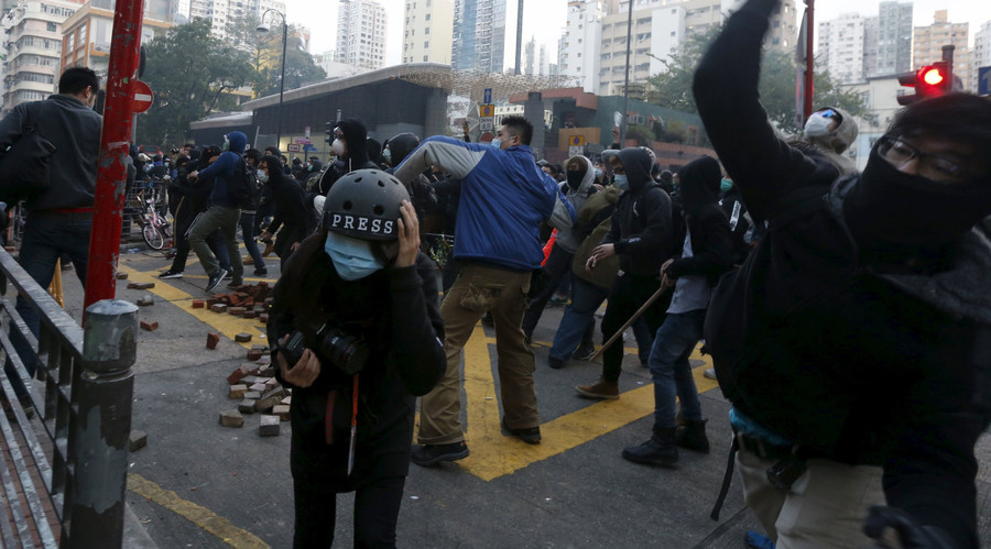 Protesters throw bricks as a journalist takes cover during a clash with riot police at Mongkok district in Hong Kong, China February 9, 2016. © Bobby Yip