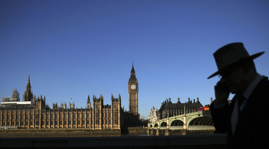 A man is silhouetted in front of the Houses of Parliament on a sunny winter's morning in London, Britain. © Neil Hall