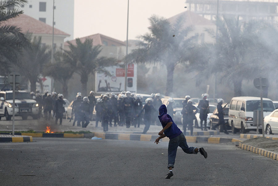 An anti-government protester throws stones towards riot police during clashes at a roundabout where an anti-government protesters staged a sit-in on Budaiya highway, west of Manama, December 18, 2011. © Hamad I Mohammed
