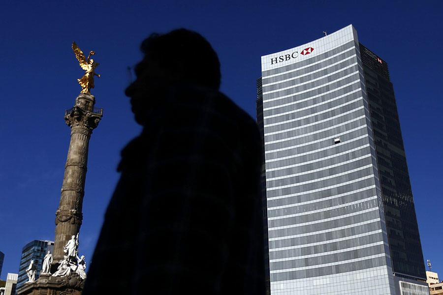 A man walks past a HSBC building near the Angel of Independence monument in Mexico City. ©Edgard Garrido