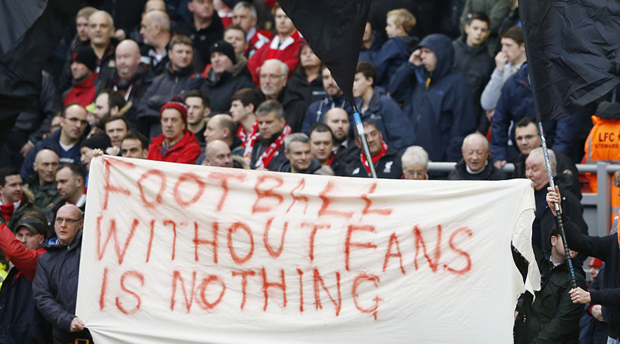 Liverpool fans hold up signs in protest against ticket prices. © Phil Noble