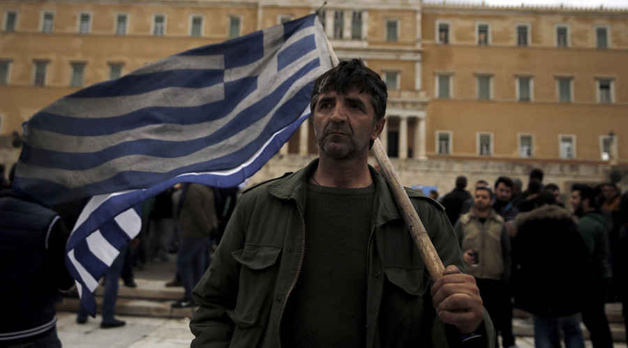 A farmer carries a Greek flag in front of the parliament during a protest against planned pension reforms in Athens, Greece February 12, 2016. © Alkis Konstantinidis