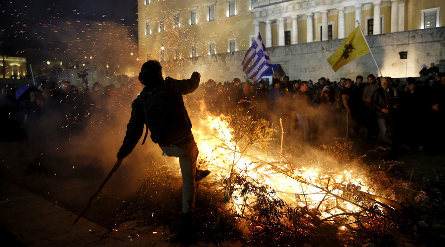 A protester is seen by a fire set by angry farmers outside the parliament during a protest against planned pension reforms in Athens, Greece February 12, 2016. © Yannis Behrakis