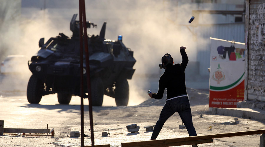 A protester throws a glass bottle containing paint at a riot police armoured personnel carrier during anti-government clashes in the village of Sitra, south of Manama, February 14, 2016 © Hamad I Mohammed