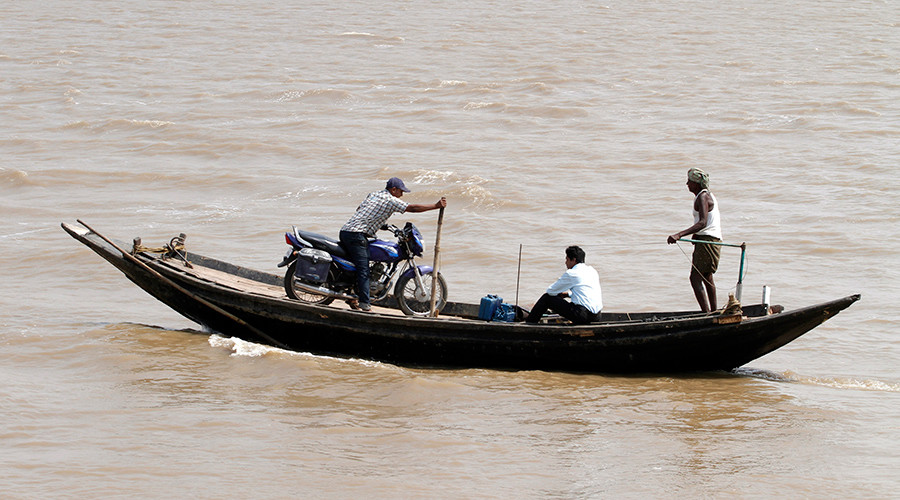 A villager balances his motorbike in a boat as he crosses the Bhitarkanika River at Gupti village in the eastern Indian state of Orissa. The BRICS New Development Bank aims to develop infrastructure projects in emerging economies © Parivartan Sharma