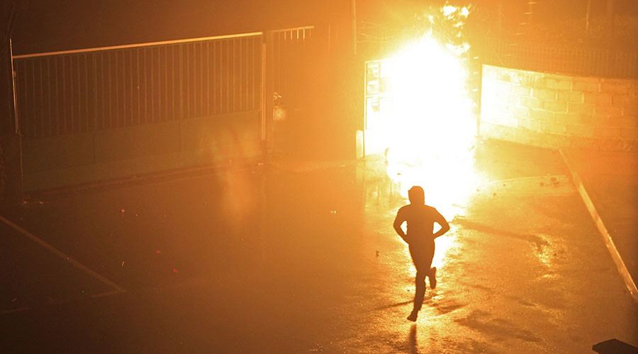 A protestor leave after a smoke bomb explode during a demonstration in the courtyard of Corte's gendarmerie, on the French Mediterranean island of Corsica, on February 15, 2016. ©Pascal Pochard Casabianca