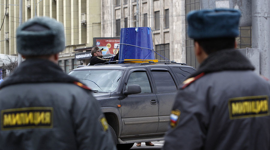 A man attaches a giant blue bucket on his car, symbolizing blue strobe lights used by emergency services and Russian VIPs to ignore traffic rules, before an automobile demonstration in Moscow. ©Sergei Karpukhin