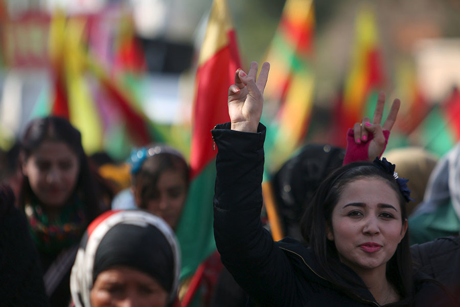 Kurdish people carry flags and flash victory signs as they take part in a protest in the city of al-Derbasiyah, on the Syrian-Turkish border, against what the protesters said were the operations launched in Turkey by government security forces against the Kurds, February 9, 2016. © Rodi Said