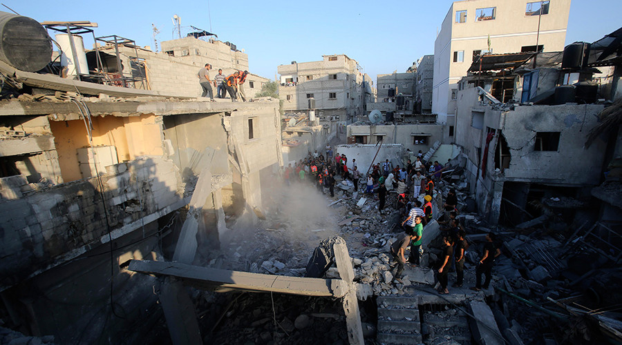 FILE PHOTO: Palestinians and rescue workers stand near the rubble of a house which police said was destroyed in an Israeli air strike in Khan Younis in the southern Gaza Strip July 10, 2014 © Ibraheem Abu Mustafa