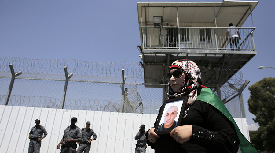 A Palestinian woman holds a picture of a Palestinian jailed in an Israeli prison during a protest calling for the prisoner's release outside the Ayalon prison, in the city of Ramle, near Tel Aviv. © Ammar Awad