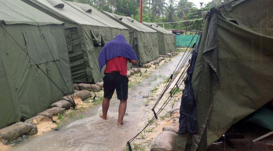 An undated photo obtained from the Refugee Action Coalition shows a man walking between tents at Australia's regional processing centre on Manus Island in Papua New Guinea. © AFP Photo
