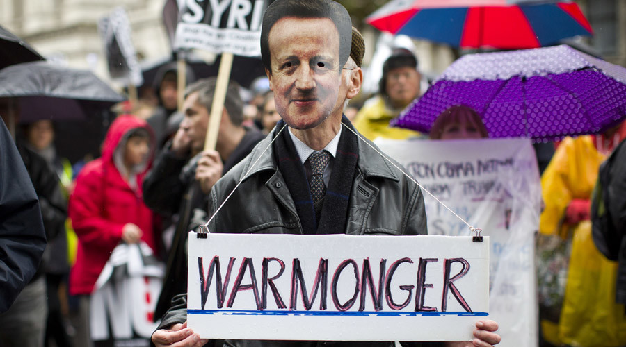 """File photo: A man wearing a British Prime Minister David Cameron mask holds a sign which reads """"Warmonger"""" stands with supporters of the 'Stop the war' coalition and 'Campaign for Nuclear Disarmament' as they march through central London © Justin Tallis"""