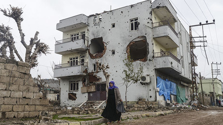 A woman walks past the ruins of a building as curfew ends during daylight in the town of Silopi on January 19, 2016. © Ilyas Akengin