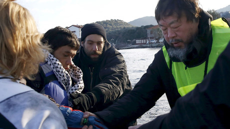 Chinese artist Ai Weiwei (R) helps an Afghan migrant as he arrives with other refugees and migrants on a raft on the Greek island of Lesbos, in this January 25, 2016 file picture. © Giorgos Moutafis
