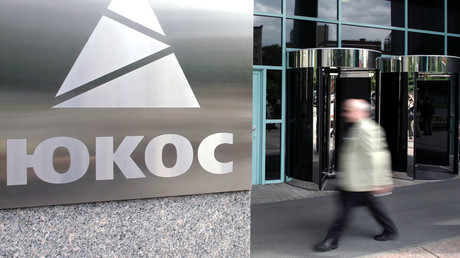 A man passes by the logo of oil giant Yukos in Moscow. © Maxim Marmur