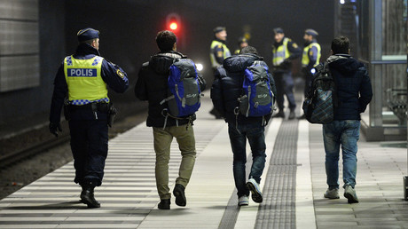 A police officer escorts migrants from a train at Hyllie station outside Malmo, Sweden. © Johan Nilsson