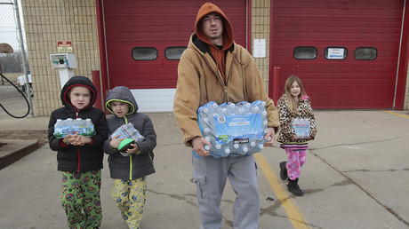 Flint resident Jerry Adkisson (2nd R) and his children Jayden (L), Austin and Amiya carry bottled water they picked up from a fire station in Flint, Michigan February 7, 2016. ©Rebecca Cook