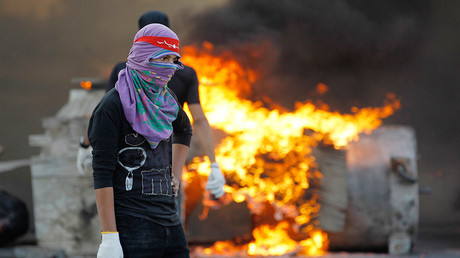A protester holding stones stands next to fire during police clashes in the village of Sitra south of Manama © Hamad I Mohammed