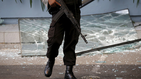 An Indonesian policeman holds a weapon while walking near a broken glass window from a Starbucks outlet in Jakarta January 14, 2016. © Beawiharta