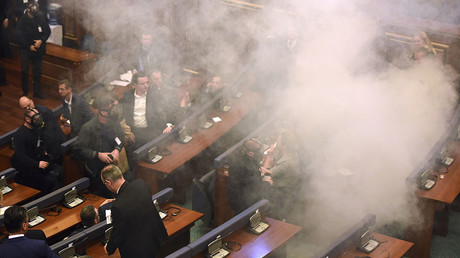 Members of the parliament disperse after a tear gas were thrown by opposition lawmakers during a extraordinary session to elect Kosovo's new President at the parliament in Pritsina on February 26,2016. © Armend Nimani