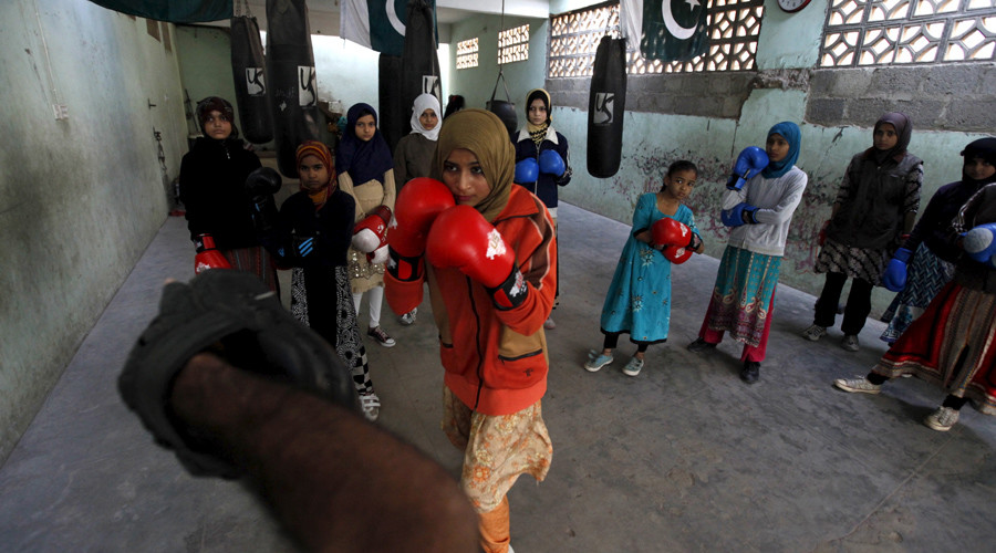 Anum, 17, punches padding with her coach Younus Qambrani while others observe during an exercise session at the first women's boxing coaching camp in Karachi, Pakistan February 20, 2016.  © Akhtar Soomro