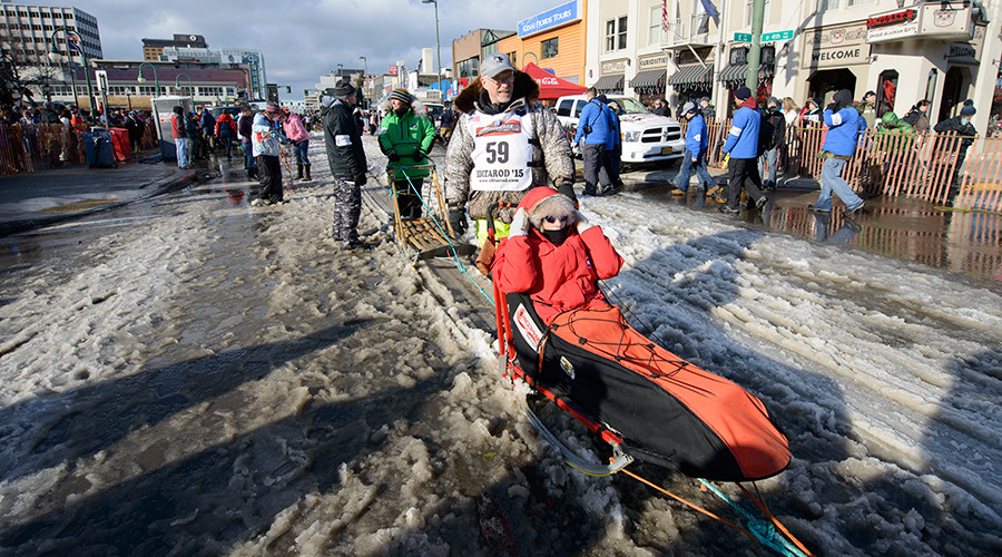 Four-time Iditarod champion Jeff King and IditaRider June Simpson (seated) navigate the slushy and quickly melting snow trucked-in and laid down on 4th avenue at the 2015 ceremonial start of the Iditarod Trail Sled Dog race in downtown Anchorage, Alaska March 7, 2015 © Mark Meyer