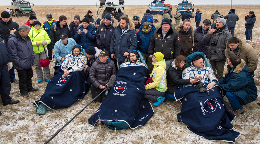 Russian cosmonauts Mikhail Kornienko (L), Sergey Volkov of Roscosmos (C), and Expedition 46 Commander Scott Kelly of NASA (R) rest in chairs outside the Soyuz TMA-18M spacecraft just minutes after they landed in a remote area near the town of Zhezkazgan, Kazakhstan © Bill Ingalls