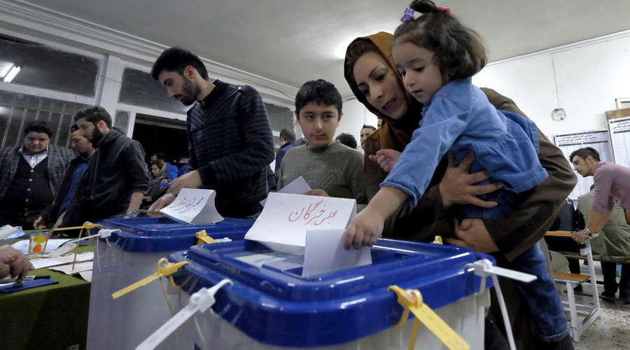 An Iranian woman holding her daughter casts her ballot during elections for the parliament and Assembly of Experts, which has the power to appoint and dismiss the supreme leader, in Tehran February 26, 2016. © Raheb Homavandi