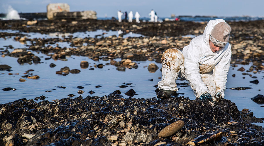 FILE PHOTO. A volunteer cleans up oil products from the coastal rocks in Nevelsk, Sakhalin Region. ©Kirill Yasko