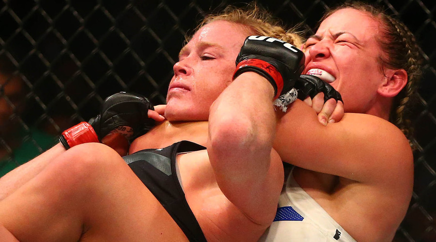 Miesha Tate applies a chokehold to win by submission against Holly Holm during UFC 196 at MGM Grand Garden Arena. © Mark J. Rebilas