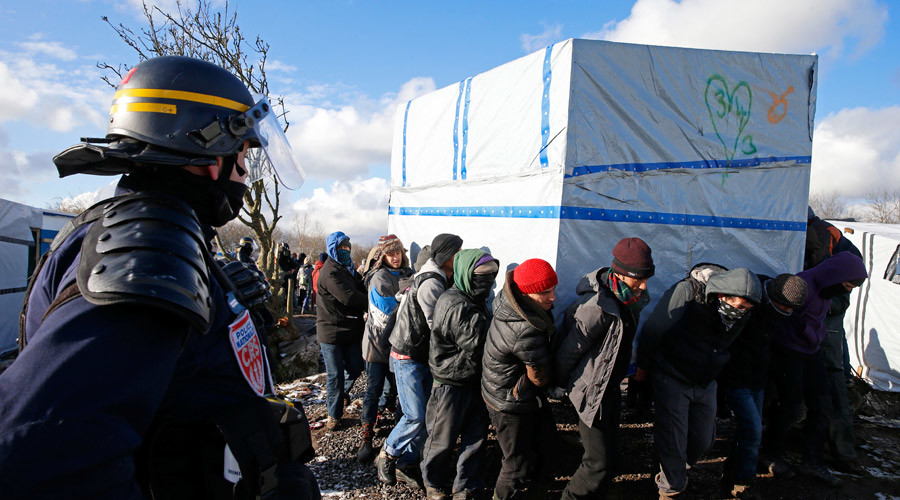 """Migrants move a makeshift shelter during the dismantlement of the southern part of the shanty town called the """"Jungle"""" in Calais, France, March 7, 2016. © Pascal Rossignol"""