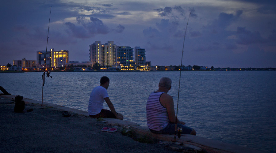 Men fish for red snapper along a causeway in Biscayne Bay at twilight in Miami © Carlo Allegri