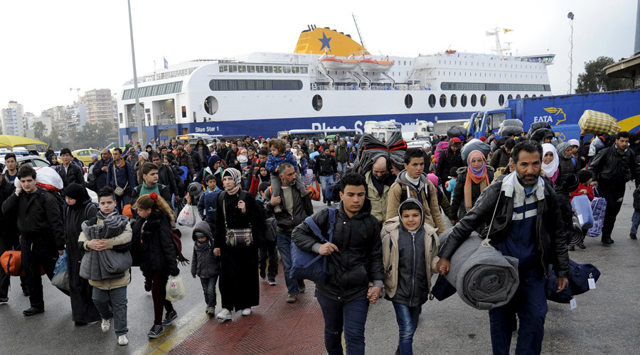 Refugees and migrants walk after disembarking from the passenger ferry Blue Star 1 at the port of Piraeus, near Athens, Greece,  March 8,  2016. © Michalis Karagiannis