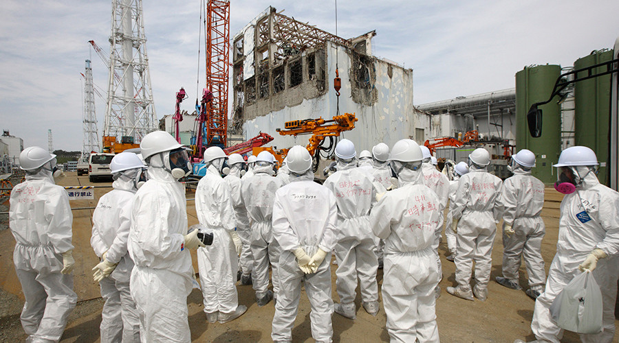 Members of the media and Tokyo Electric Power Co. (TEPCO) employees, wearing protective suits and masks, look at the No. 4 reactor building (C) at the tsunami-crippled Fukushima Daiichi nuclear power plant in Fukushima prefecture May 26, 2012 © Tomohiro Ohsumi