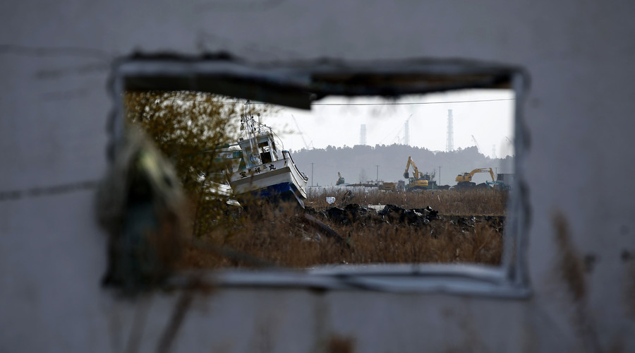 A fishing boat washed up by the March 11, 2011 tsunami and black plastic bags containing radiated soil, leaves and debris from the decontamination operation are seen in front of cranes and chimneys of Tokyo Electric Power Co's (TEPCO) Fukushima Daiichi nuclear power plant. © Toru Hanai